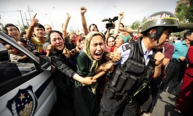 Polícia repreende manifestantes da etnia uigur durante protesto em Xinjiang Foto: PETER PARKS / Arquivo