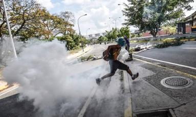 Uma ativista da oposição venezuelana entra em confronto com a polícia durante protesto contra o presidente Nicolás Maduro Foto: JUAN BARRETO / AFP