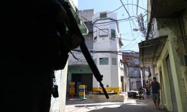 Policial faz a segurança para a instalação da torre blindada no Largo do Samba Foto: Marcia Foletto / Marcia Foletto