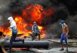 Manifestantes montam barricada durante protesto contra o presidente Nicolás Maduro em Caracas Foto: CHRISTIAN VERON / REUTERS