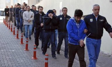 Policiais escoltam pessoas presas por suspeitas de ligações com o clérigo americano Fethullah Gulen, em Kayseri, na Turquia Foto: Olcay Duzgun / DHA-Depo Photos