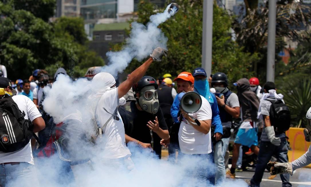 Manifestante arremessa lata de gás lacrimogêneo durante protesto em Caracas, capital venezuelana. Foto: CARLOS GARCIA RAWLINS 26/04/2017 / REUTERS