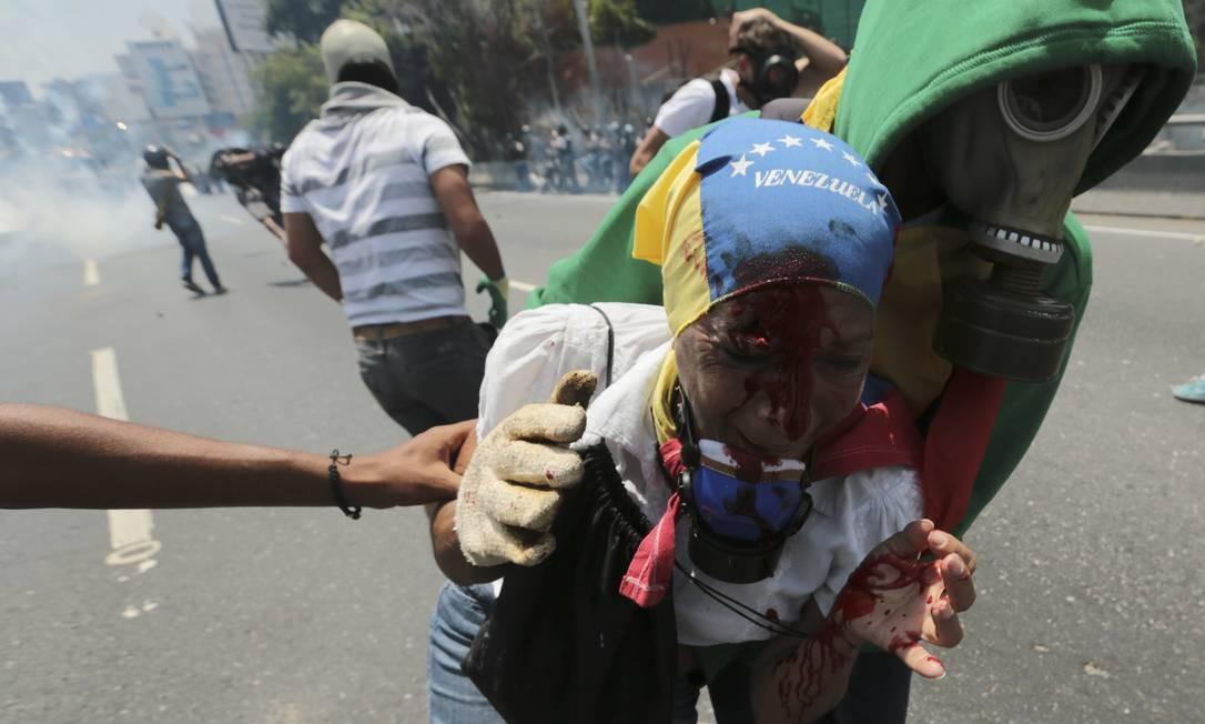 Mulher ferida durante protestos contra Maduro é auxiliada por um manifestante. Foto: Fernando Llano 26/04/2017 / AP