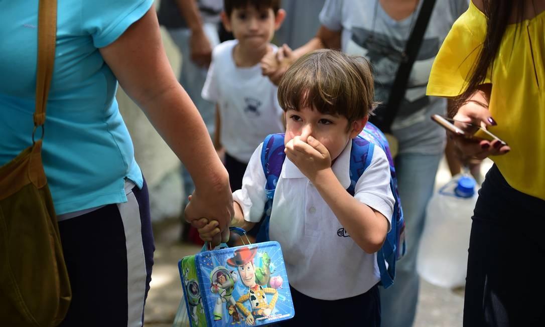 Criança cobre o nariz para não inalar gás lacrimogeneo disparado pela polícia contra os manifestantes que marchavam contra Maduro. Foto: RONALDO SCHEMIDT 26/04/2017 / AFP