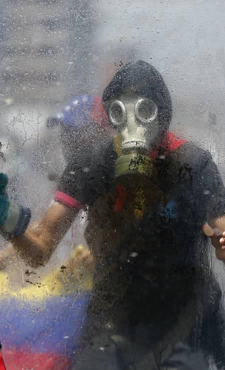 Manifestante se protege da violência dos protestos com um escudo de acrílico improvisado. A Venezuela está ameaçando se retirar da OEA como resposta do governo socialista às agitações políticas que já vitimaram 28 pessoas, de acordo com dados oficiais. Foto: Ariana Cubillos 26/04/2017 / AP