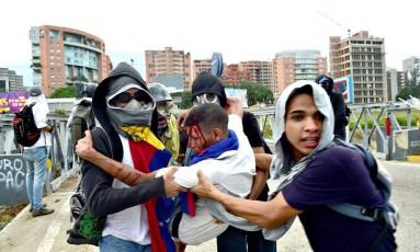 Ativista da oposição é caregado após ser ferido em protesto em Caracas Foto: RONALDO SCHEMIDT / AFP