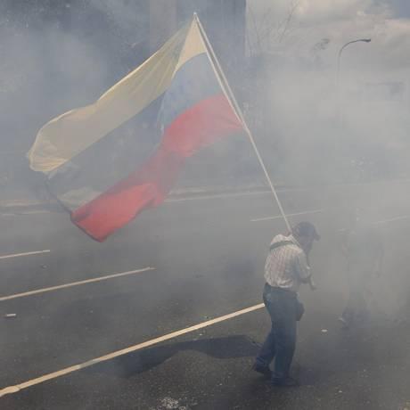 Homem carrega bandeira da Venezuela no meio do gás lacrimogêneo lançado pela polícia em protesto Foto: Ariana Cubillos / AP