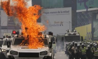 Veículo da polícia pega fogo após bombas terem sido lançadas por manifestantes contra Maduro em Caracas Foto: Fernando Llano / AP