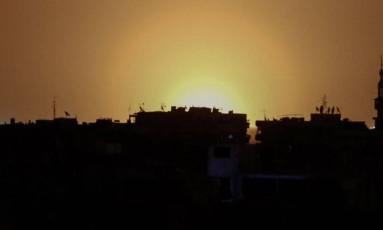 Foto tirada de cidade rebelde mostra o que aparentam ser chamas perto do aeroporto de Damasco Foto: AFP