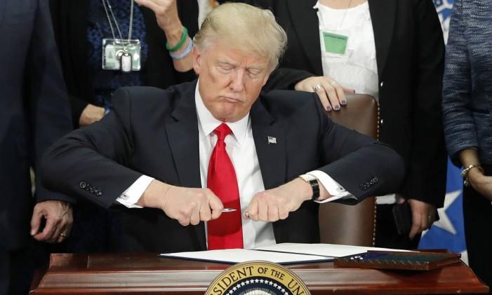 O presidente dos EUA, Donald Trump, tira a tampa de uma caneta antes de assinar uma ordem de ações contra a imigração, em Washington Foto: Pablo Martinez Monsivais / AP