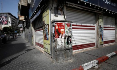 Cartaz com foto de líder palestino preso foi pregado na frente de lojas fechadas em paralisação de apoio a detentos em greve de fome Foto: MOHAMAD TOROKMAN / REUTERS