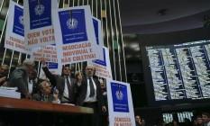 Oposição protesta com cartazes contra a reforma trabalhista, enquanto o relator lê o texto. Foto Aílton de Freitas/Agência O Globo