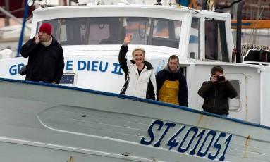 A candidata à Presidência francesa do partido de extrema-direita Frente Nacional (FN), Marine Le Pen, acena de um barco após encontrar pescadores em Le Grau-du-Roi, no Sul da França, nesta quinta-feira Foto: BERTRAND LANGLOIS / AFP