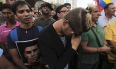 Um homem segura uma foto de Juan Pablo Pernalete no local onde ele foi morto em Caracas, na Venezuela, durante os protestos contra o presidente Nicolás Maduro Foto: Fernando Llano / AP