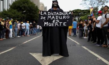 """Partidário da oposição segura cartaz com a mensagem: """"A ditadura de Maduro é morte' Foto: CARLOS GARCIA RAWLINS / REUTERS"""
