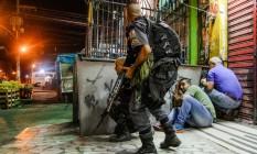 Tensão. Policiais e moradores do Complexo do Alemão se protegem durante um tiroteio: Foto: Bruno Itan