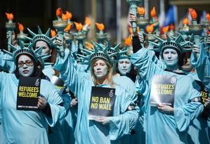Ativistas da Anistia Internacional realizam protesto vestidos como Estátuas da Liberdade, em frente à embaixada americana em Londres Foto: NIKLAS HALLE'N / AFP