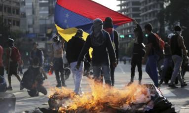 Manifestantes bloqueiam viam em Caracas durante protesto contra o presidente Nicolás Maduro Foto: Fernando Llano / AP