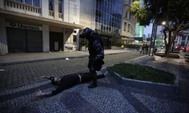 Manifestante caído é abordado por policial durante protesto. Confronto começou durante protesto em frente à Alerj Foto: Pablo Jacob / Agência O Globo