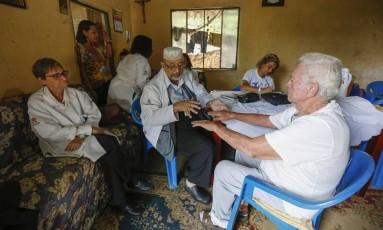 A equipe do Padi Ilha durante encontro com família na comunidade Boogie Woogie Foto: Marcelo de Jesus / Agência O Globo