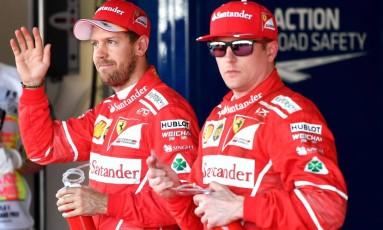 Os pilotos da Ferrari Sebastian Vettel e Kimi Raikkonen comemoram o primeiro e o segundo lugares do grid, respectivamente, no GP da Rússia Foto: ANDREJ ISAKOVIC / AFP