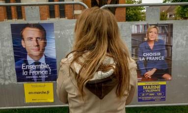 Mulher observa cartezes dos dois candidatos à presidência na França Foto: PHILIPPE HUGUEN / AFP