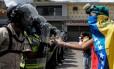 Manifestante venezuelano gesticula para policiais em Caracas