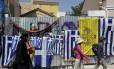 Pessoas caminham em rua de Atenas com bandeiras da Grécia. Foto: Thanassis Stavrakis/AP