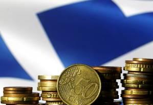 Moedas de euro com a bandeira da Grécia ao fundo. Crédito: Dado Ruvic/Reuters