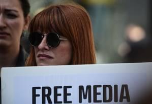 Jornalista segura cartaz em que se lê