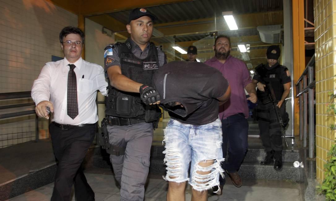 PM com o rosto escondido deixa a delegacia da Pavuna. À esquerda, de branco, advogado da Associação de Policiais Militares do Estado do Rio Foto: Pedro Teixeira / Agência O Globo