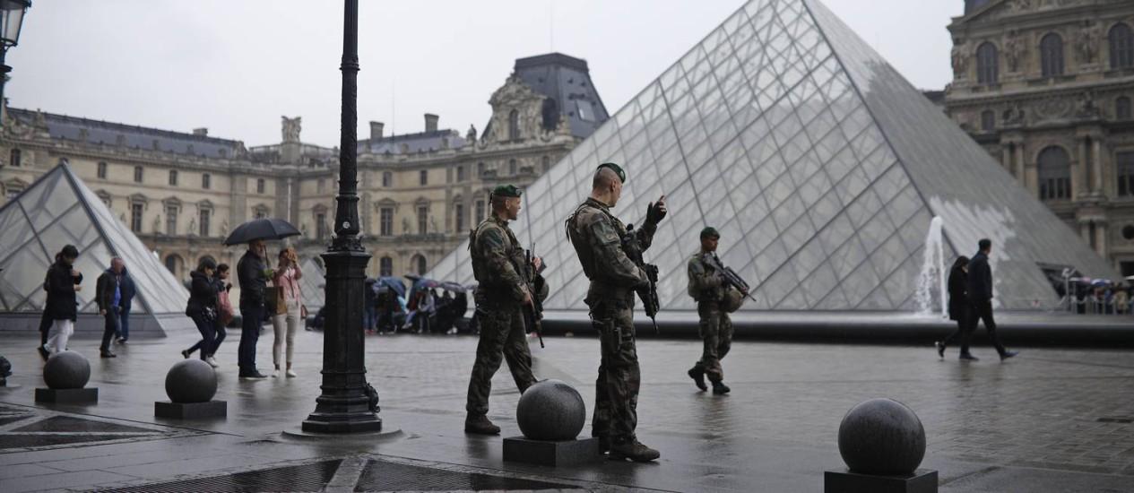 Soldados patrulham o pátio em frente ao Museu do Louvre, em Paris, que foi evacuado depois que uma mala suspeita foi encontrada no local onde o candidato centrista à Presidência Emmanuel Macron estava previsto para discurdar neste domingo Foto: Kamil Zihnioglu / AP