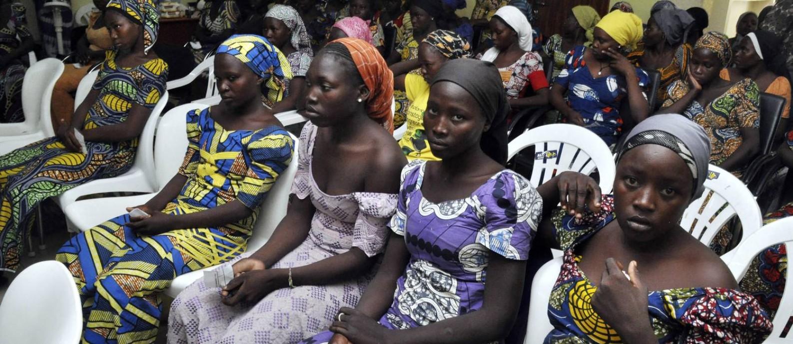 As meninas libertadas pelo Boko Haram esperam para se reunirem com suas famílias antes de encontro com o presidente da Nigéria, Muhammadu Buhari Foto: Olamikan Gbemiga / AP