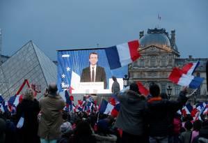 Presidente eleito Emmanuel Macron é visto em uma tela gigante perto do Louvre, em Paris, enquanto partidários celebram sua vitória Foto: JEAN-PAUL PELISSIER / REUTERS