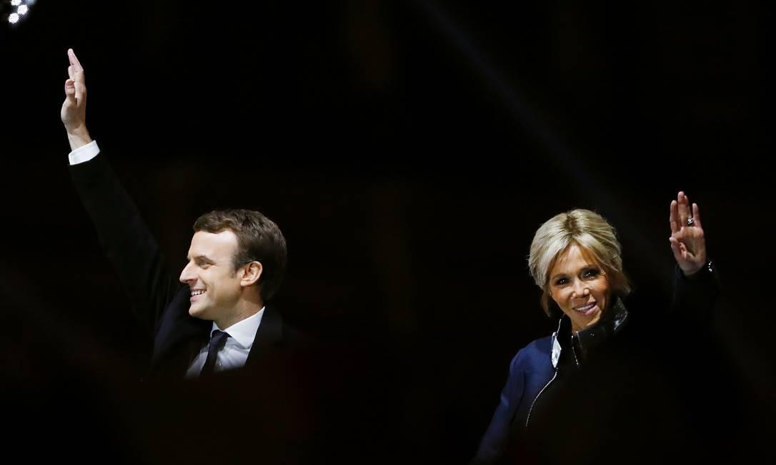 Futuros presidente e primeira-dama da França, Emmanuel e Brigitte Macron acenam a multidão; candidato centrista derrotou a candidata da extrema-direita, Marine Le Pen, com 66% dos votos Foto: PATRICK KOVARIK / AFP