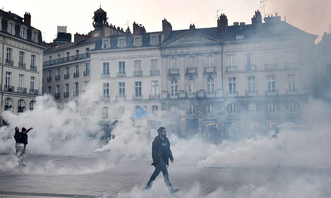 Manifestantes caminham por nuvens de gás lacrimogêneo lançada durante protestos após eleições em Paris Foto: JEAN-SEBASTIEN EVRARD / AFP