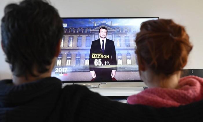 Casal assiste a um canal de TV anunciando o novo presidente francês, em Hede-Bazouges, na France Foto: DAMIEN MEYER / AFP
