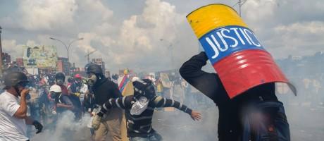Homem se protege com um escudo durante confrontos entre manifestantes e forças de seguranças, na Venezuela Foto: JUAN BARRETO / AFP