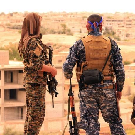 Combatentes das FDS observam cidade síria de Tabqa, local estratégico para derrota o Estado Islâmico no país Foto: Uncredited / AP