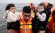 Refugiado carrega crianças na chegada à ilha grega de Lesbos, porta de entrada para a Europa