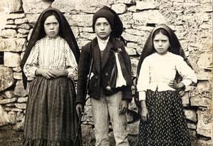 A imagem mais famosa dos três pastorinhos de Fátima. Lúcia, à, esquerda, era a mais velha e a única que dizia ver, ouvir e falar com a santa. Francisco, no meio, dizia que via a Virgem Maria, mas não a escutava nem falava com ela. E Jacinta, à direita, afirmava ver e ouvir Nossa senhora, mas não podia se comunicar Foto: HO / AFP