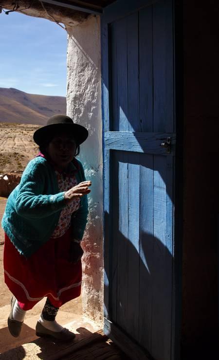 E no povoado de Machuca, no Chile, uma senhora com vestimenta característica dessa região guarda a igreja da vila Foto: Daniel Marenco / Agência O Globo