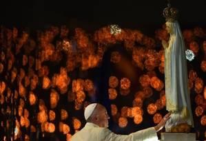 Iluminado pelas velas dos fiéis ao fundo, Papa reza diante da estátua de Fátima em capela do Santuário Foto: PATRICIA DE MELO MOREIRA/AFP