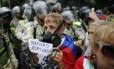 Mulher exibe mensagem chamando Maduro de assassino durante protesto em Caracas