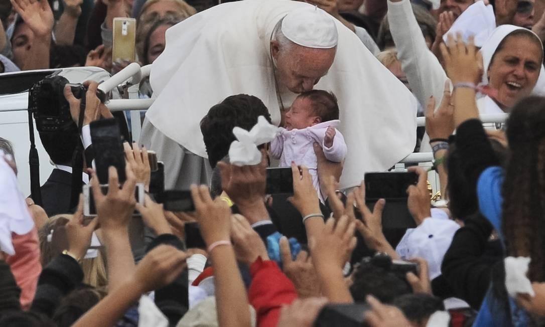 A Papa Francisco para para beijar um bebê antes de deixar o Santuáriode Nossa Senhora de Fátima Foto: Paulo Duarte / AP