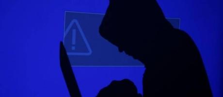 Homem com capuz em computador Foto: Kacper Pempel / Rueters