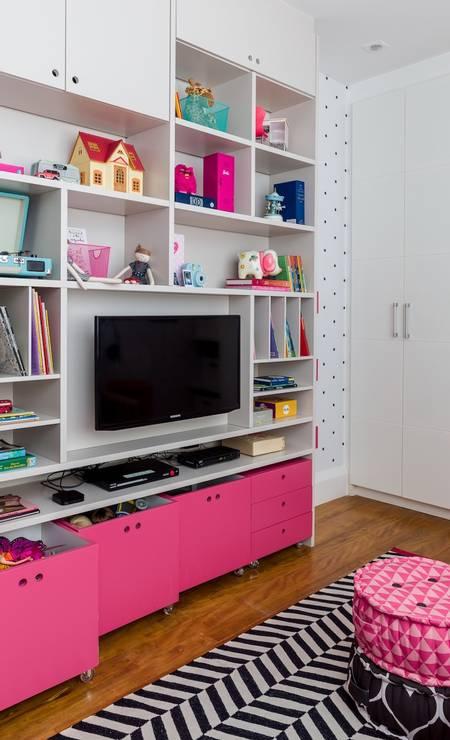 Como Julia tem muita coisa pra guardar, foi fundamental pensar em espaço para arrumar tudo. Uma generosa estante foi desenhada para a TV, com nichos abertos e fechados com lugar para acomodar jogos, brinquedos, livros, objetos, etc Foto: Nicolas Bouriette / Divulgação