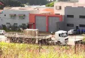 O galpão (cinza) alugado pela quadrilha uniformizada de azul, com o caminhão à frente que transportava a droga Foto: Reprodução/TV Globo