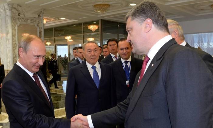 O presidente da Rússia, Vladimir Putin, e o presidente da Ucrânia, Petro Poroshenko, se cumprimentam durante um encontro em agosto de 2014 Foto: SERGEI BONDARENKO / AFP