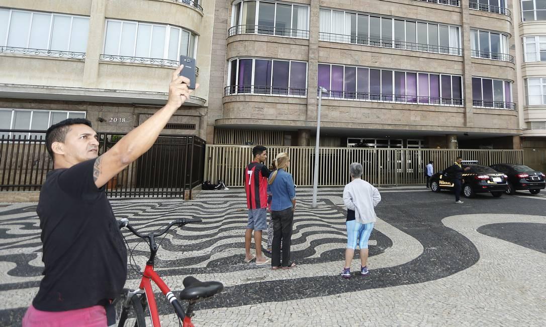 Povo faz selfies e tenta saber notícias ao ver carro da Federal em frente à casa da irmã de Aécio, Andréa Neves Foto: Antonio Scorza / O Globo